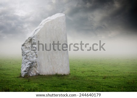 Blank grunge white tombstone on a green meadow - stock photo
