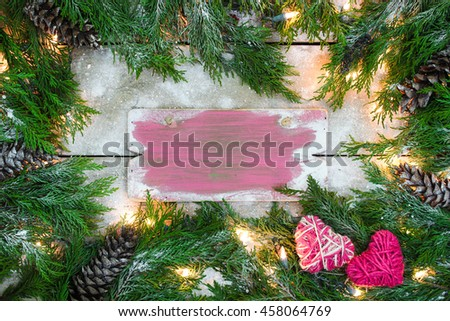 Blank holiday sign with green Christmas tree garland border, pink rope hearts, snow and lights on antique rustic wood background; love concept - stock photo