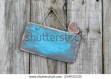 Blank ice teal blue antique wood sign with heart hanging on rustic wooden background - stock photo