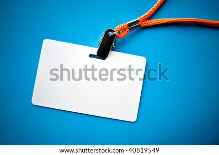 Blank ID card / badge with copy space, isolated on blue. - stock photo
