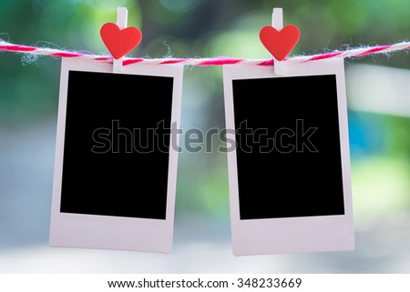 Blank instant  photo and red clip paper heart hanging on the clothesline with bokeh nature background.Designer concept. - stock photo