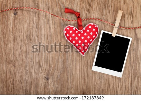 Blank instant photo and red heart hanging. On wooden background with copy space - stock photo