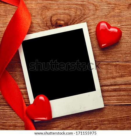 Blank instant photo and small red hearts with ribbon on old dark grunge background - stock photo