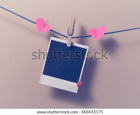 Blank instant photo and small red paper heart. - stock photo