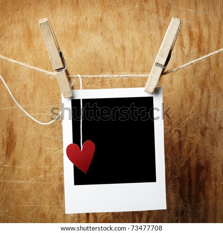 Blank instant photo and small red paper heart hanging on the clothesline. On dark grunge background. - stock photo