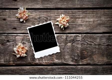 Blank instant photo frame with dried flowers on old wooden background. - stock photo
