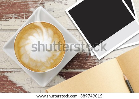 Blank Instant photo frames, notebook and cup of coffee on vintage wood table - stock photo