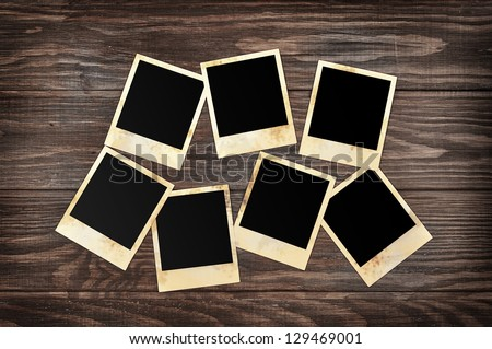 Blank instant photo frames on old wooden background. Clipping path included. - stock photo