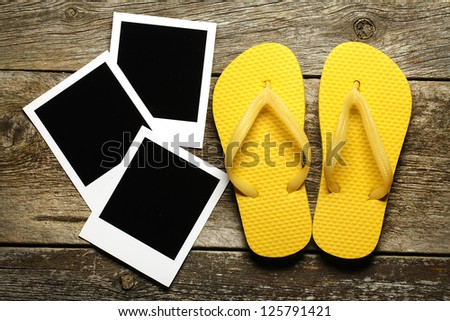 Blank instant photo frames with colored flip-flops on wood - stock photo