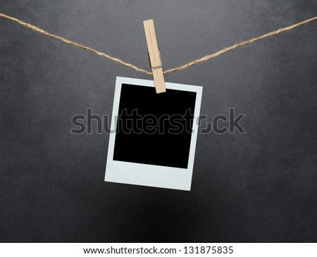 Blank instant photo hanging on the clothesline over concrete wall with clipping path for the inside of the frame - stock photo