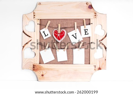 Blank instant photos and red plush heart hanging on the clothesline with sackcloth and wooden frame on background - stock photo