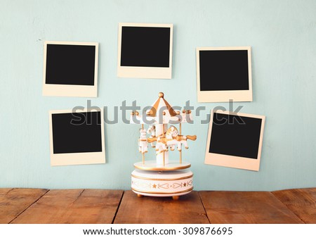blank instant photos hang over wooden textured background next to vintage white carousel horses  - stock photo