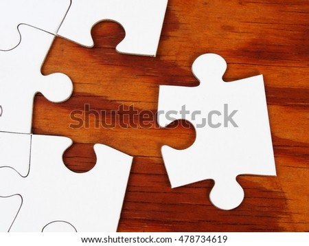 Blank jigsaw puzzle with last piece on wooden table