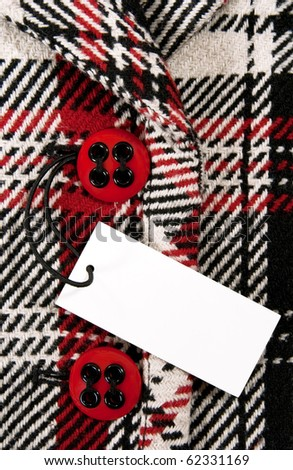 Blank label or price tag attached to a button of a stylish red checked coat.