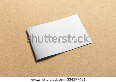 Blank landscape, brochure magazine isolated on cardboard background, with clipping path, changeable background - stock photo