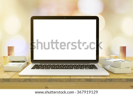Blank laptop screen on the wooden table with bundles of money and piles of gold coins, mock up - stock photo