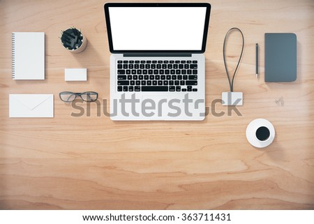 Blank laptop screen with office accessories on wooden table, mock up - stock photo