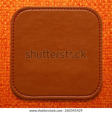 Blank leather brown label on fabric background - stock photo