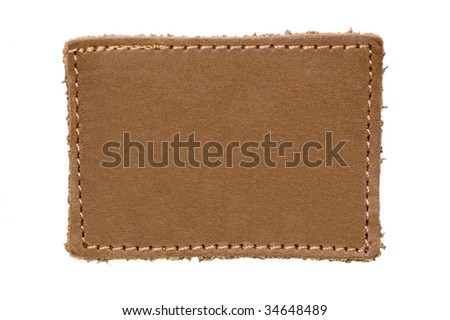 Blank leather label, isolated beige jeans tag closeup, macro, natural rustic background - stock photo