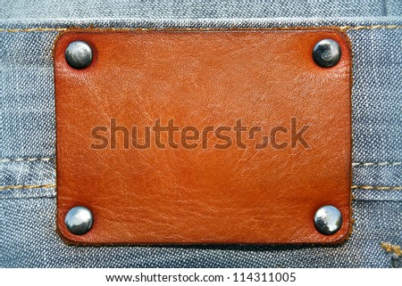 Blank leather label over blue jeans background with metal rivets - stock photo