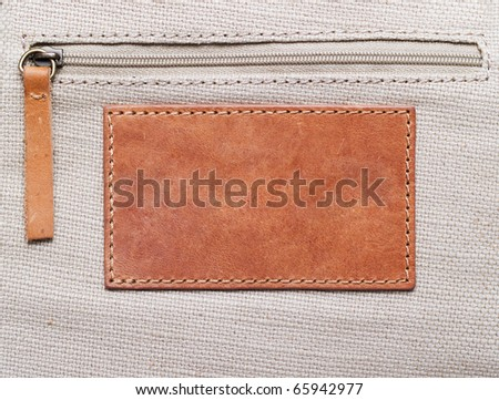 blank leather label stitched onto the canvas with zipper - stock photo