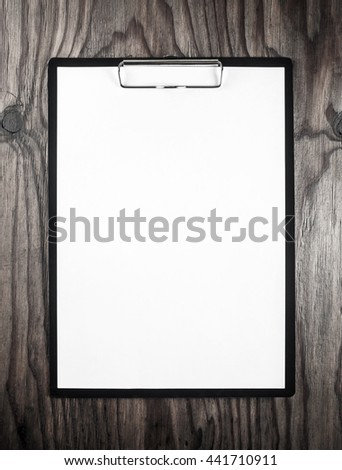 Blank letterhead. Blank sheet of paper in clipboard on dark wooden table background. Blank template for design portfolios. Mock-up for your design. - stock photo