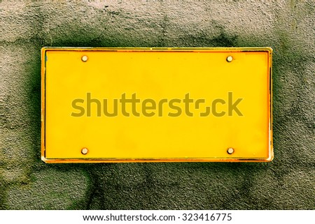 blank license plate on dark crack wall background ,vintage tone - stock photo
