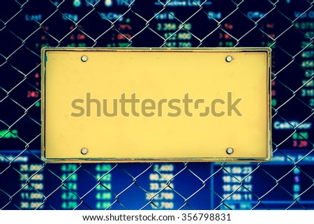 blank license plate on net fence and blur stock market number background