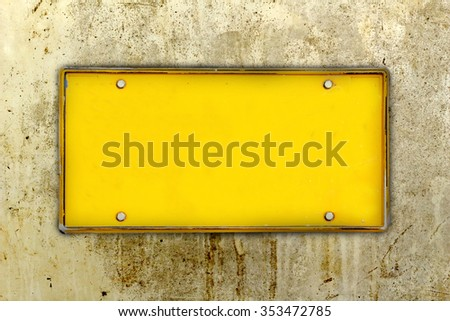 blank license plate with dirty wall background - stock photo
