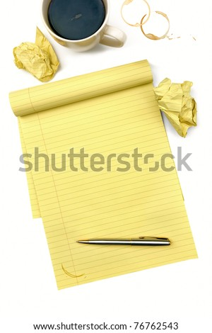 Blank lined notepad with pen, cup of coffee, and crumpled balls of paper. - stock photo