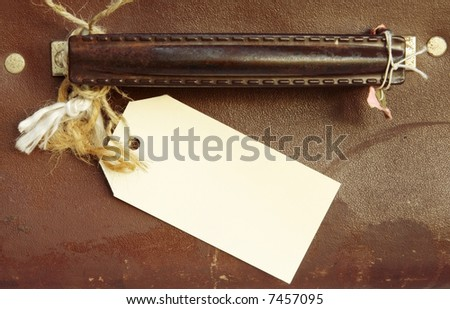 Blank luggage label tied to handle of vintage leather suitcase. - stock photo