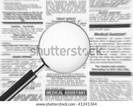 Blank magnifying glass over newspaper. Plenty of room to add text to display your message - stock photo