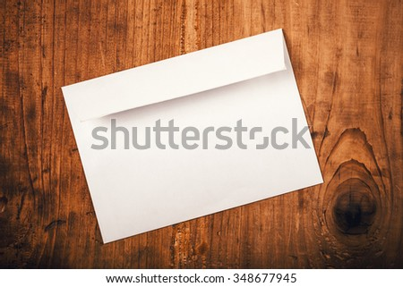 Blank mailing envelope on top of working office desk as copy space, top view - stock photo