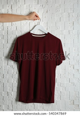 Blank maroon t-shirt against light textured background