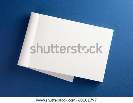 Blank memo pad with page folded back on blue surface. - stock photo