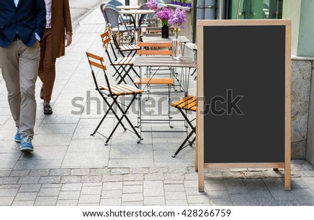 Blank menu blackboard on the street with cafe chairs and people passing by - stock photo