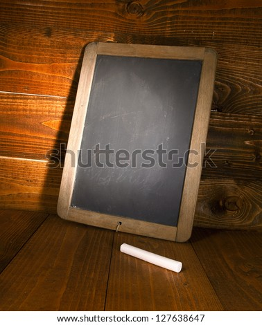 Blank menu board with a piece of chalk, on a wooden background