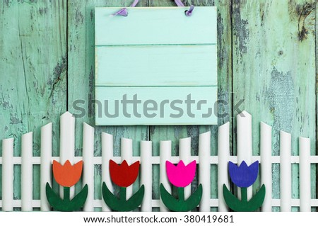 Blank mint green wood sign hanging over white picket fence with row of colorful spring flowers on antique rustic wooden background; purple, pink, orange, red tulips - stock photo