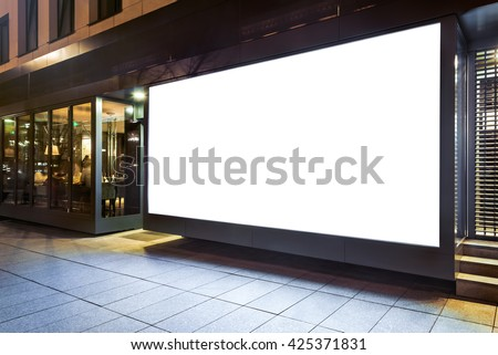 Blank mock up of store street showcase window in a city at night - stock photo