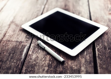 Blank modern digital tablet on a wooden desk. Digital tablet computer with isolated screen on wooden table - stock photo