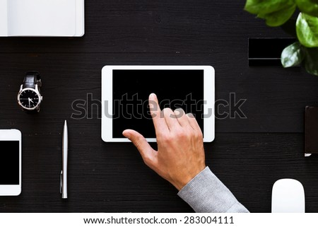 Blank modern digital tablet on a wooden desk. Top view. Great for your copy space. Gadgets on a wooden desk background. View from above. - stock photo
