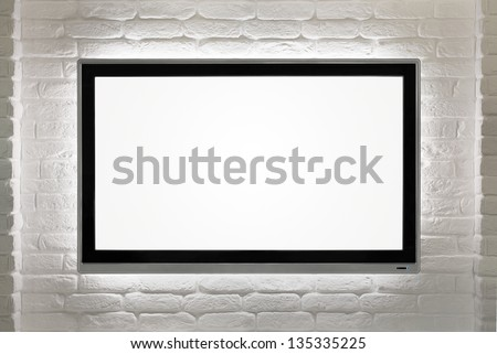 Blank modern flat screen TV at the white brick wall with copy space - stock photo