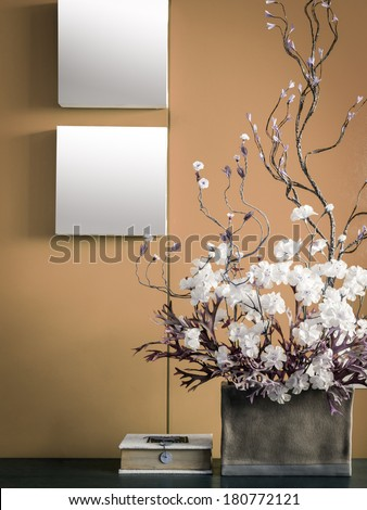 Blank modern interior wall decorate with artificial flowers in ceramic vase - stock photo