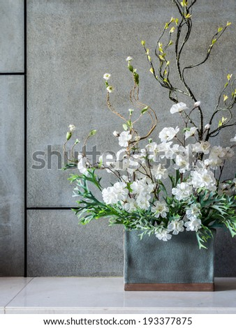Blank modern interior wall with artificial flowers in ceramic vase - stock photo
