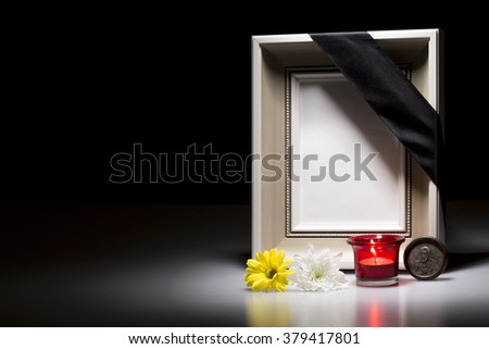blank mourning frame with flower and candle on dark background - stock photo