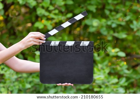 Blank movie clapper board in hands outdoors - stock photo