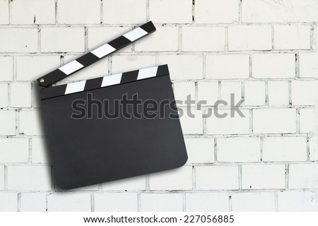 Blank movie production clapper board against a brick wall - stock photo