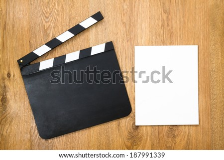 Blank movie production clapper board with blank paper against wooden background  - stock photo