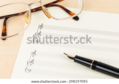 Blank music score on cream color paper with glasses and pen - stock photo
