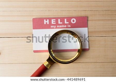 Blank name tag with magnifier glass - stock photo